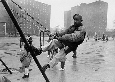 Girl on a swing in front of the Darrow Homes
